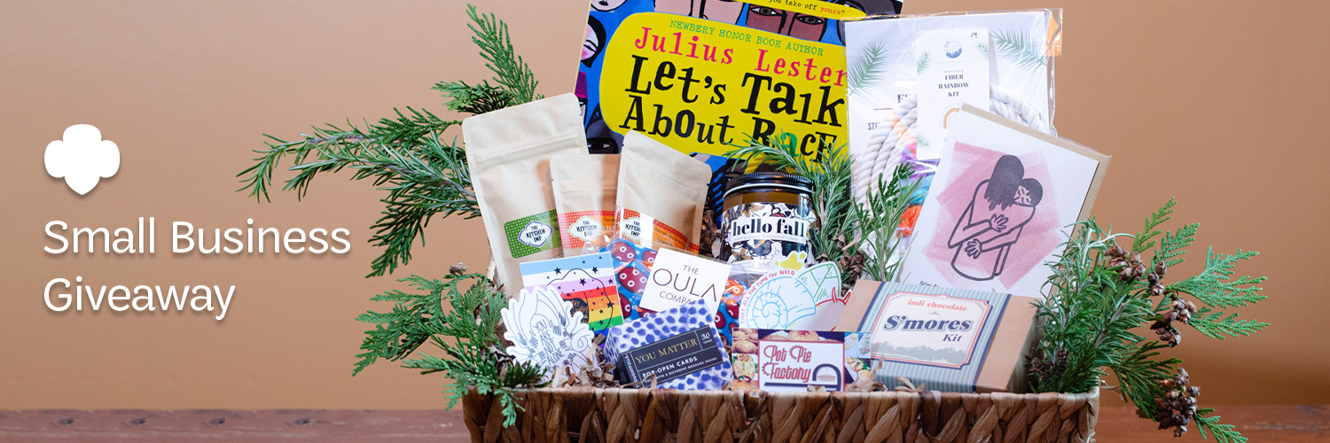 "A large woven basket, filled with colorful items from western Washington small businesses and decorative coniferous foliage, with a white Girl Scout trefoil and text that says, ""Small Business Giveaway"" at the side with a warm-colored backdrop."