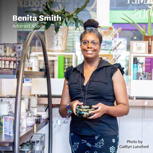 "Bentia Smith stands in her store, Adorned Abode holding a tinned candle, surrounded by colorful shop items and plants, with white text that says, ""Benita Smith, Adorned Adobe"" at the top and, ""Photo by Caitlyn Lunsford"" at the bottom in black text."
