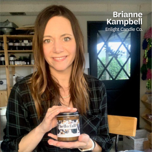 "Brianne Kampbell, the owner of Enlight Candle Co., holds up a Hello Fall scented candle in her studio, with text that says, ""Brianne Kampbell, Enlight Candle Co."" at the top in white text."