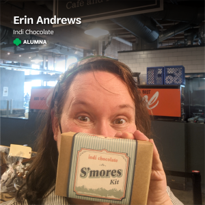 "Erin Andrews, the owner of Indi Chocolate, holds up a s'mores kit from Indi Chocolate, with text that says, ""Erin Andrews, Indi Chocolate, Alumna"" at the top with a small green trefoil."