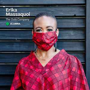 "Erika Massaquoi, the founder and CEO of The Oula Company, wears a vibrant red Ankara face mask and matching dress, against a dark backdrop with text that says, ""Erika Massaquoi, The Oula Company, Alumna"" at the top with a small green trefoil."