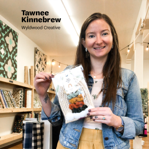 "Tawnee Kinnebrew, the owner of Wyldwood Creative, holds up a macrame Rainbow Fiber Kit inside her Renton store, with text that says, ""Tawnee Kinnebrew, Wyldwood Creative"" at the top."