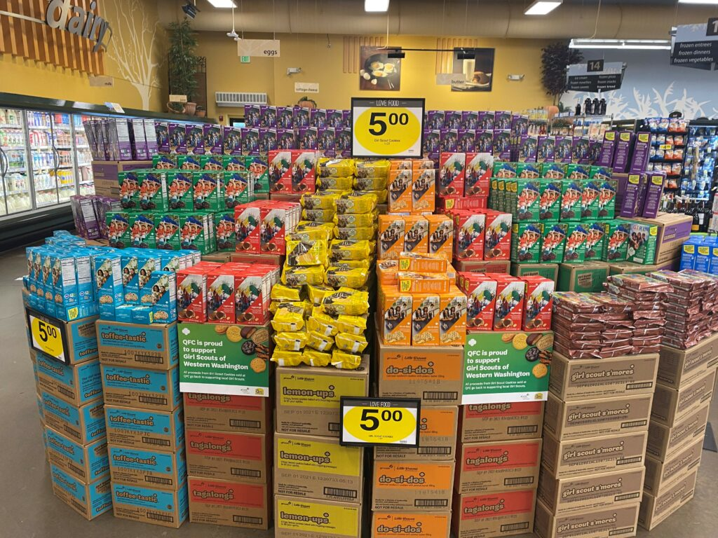 Display of Girl Scout Cookie boxes in a grocery store.