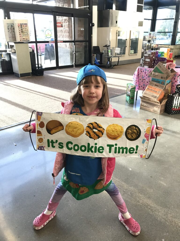 """A Daisy Girl Scout holds a banner with Girl Scout Cookies and the words, """"It's Cookie Time!"""""""